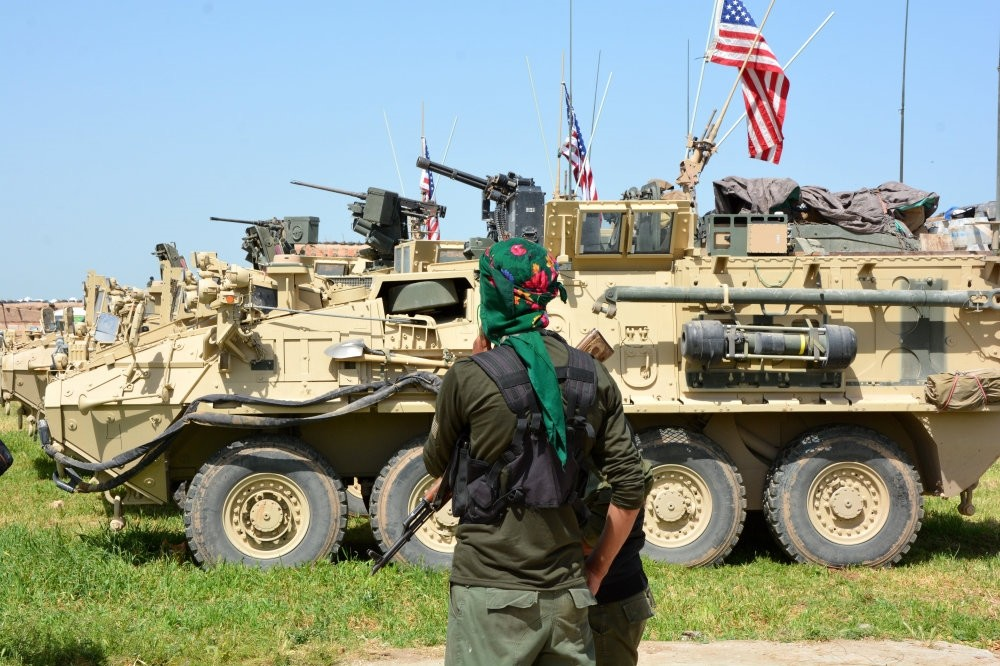 A YPG terrorist stand next to the U.S. eight-wheeled armored fighting vehicles, near al-Ghanamya village, al-Darbasiyah town at the Syrian-Turkish border on April 29.