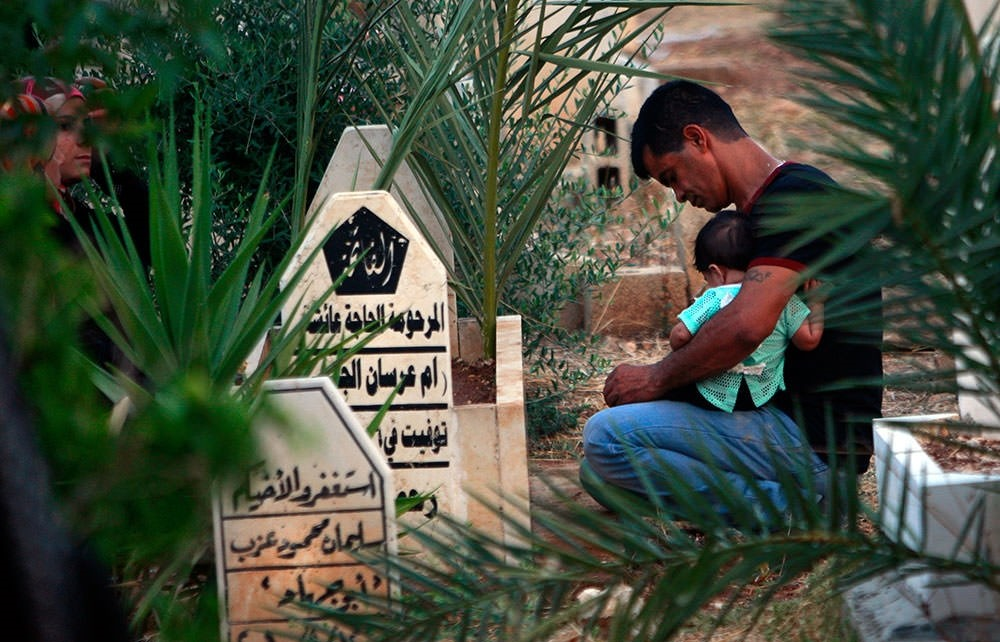 A Palestinian Muslim for his deceased relative on the first day of Eid al-Fitr