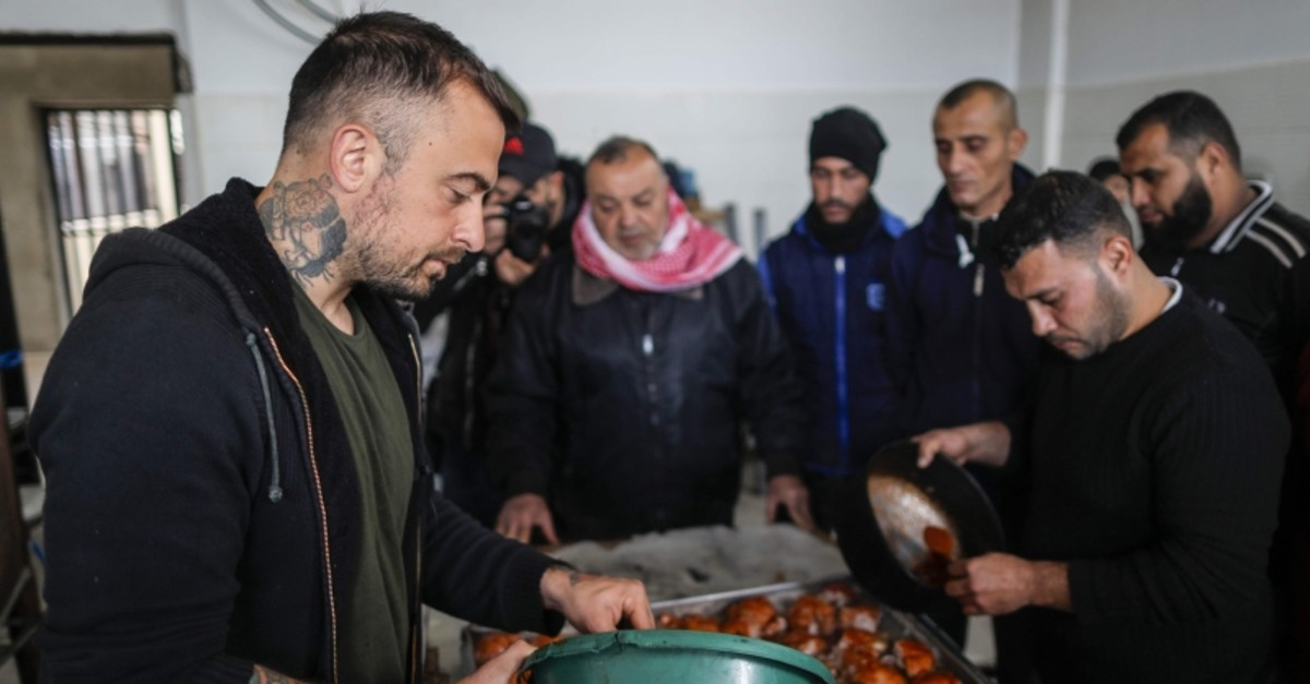 Gabriele Rubini (L), known as Chef Rubio, cooks with Palestinian prisoners at a Hamas-run civilian prison in Gaza City on January 21, 2020, where he is teaching the inmates how to cook Italian food and they teach him Palestinian recipes. (AFP Photo)