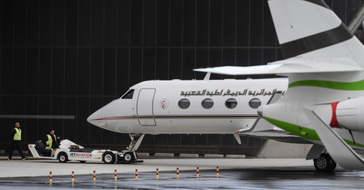 Staff members take an Algerian government plane - believed to be carrying President Abdelaziz Bouteflika - out a hangar prior to taking off from Geneva airport, on March 10, 2019. (AFP Photo)