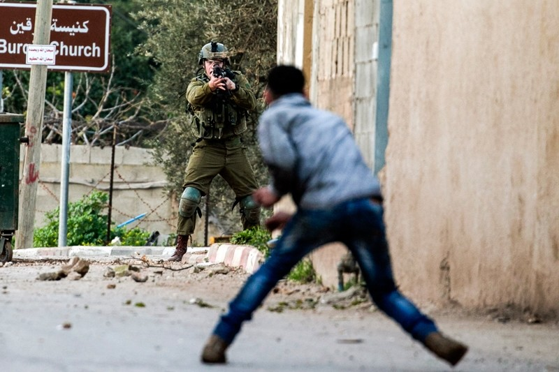 A Palestinian protester confronts an Israeli soldier during an army search operation in the Palestinian village of Burqin in the occupied West Bank, on February 3, 2018. (AFP Photo)