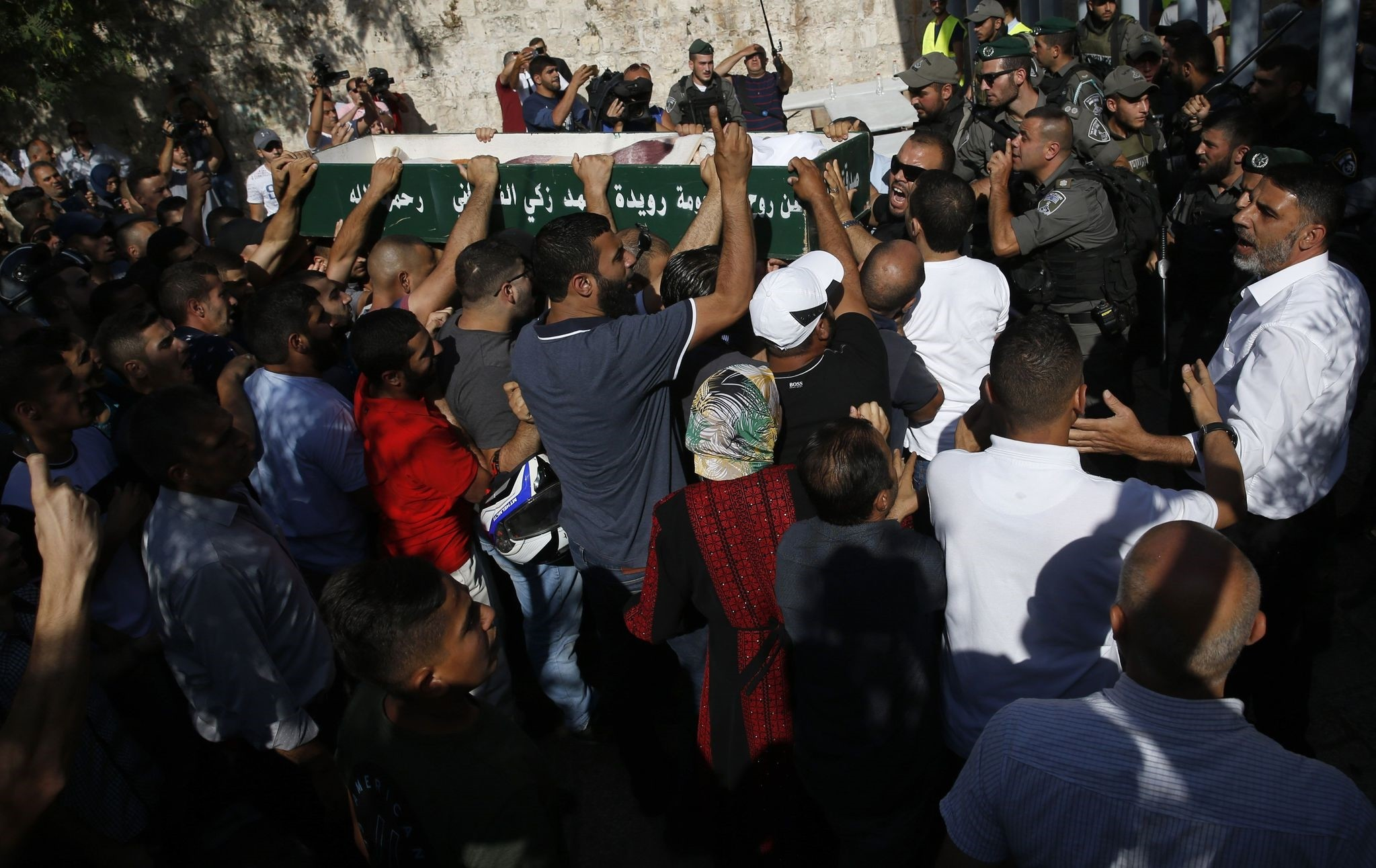Palestinian mourners carry a coffin outside Al-Aqsa mosque compound as they refuse to undergo checking by Israeli (AFP PHOTO)