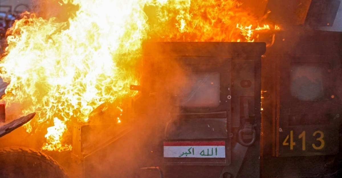 A riot police vehicle burns during clashes amidst demonstrations against state corruption, failing public services, and unemployment in the Iraqi capital Baghdad's central Tayeran Square on October 3, 2019. (AFP Photo)