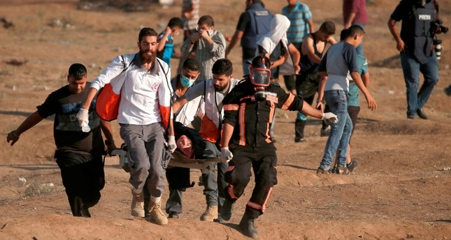 Palestinian protesters carry a man injured during a demonstration along the border between Israel and the Gaza strip, east of Gaza city on July 27, 2018. (AFP PHOTO)