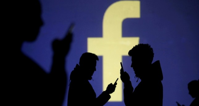 Silhouettes of mobile users are seen next to a screen projection of Facebook logo in this picture illustration taken March 28, 2018. (Reuters Photo)