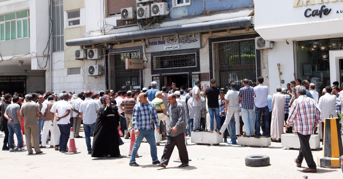 People form long lines in front of a bank in Tripoli, Libya.