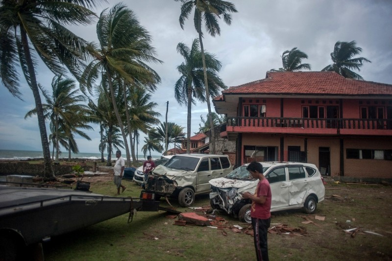 Owners reclaim their damaged cars from a resort affected by Saturday's tsunami in Carita, Indonesia, Tuesday, Dec. 25, 2018. (AP Photo)