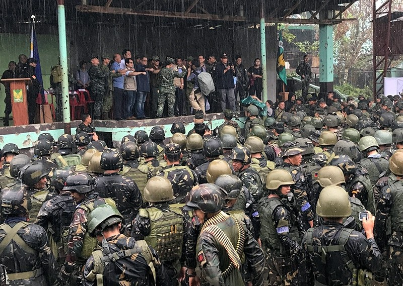 Philippine President Rodrigo Duterte, center, is joined by other government and military officials as they visit troops in Marawi, southern Philippines on Tuesday Oct. 17, 2017 (AP Photo)