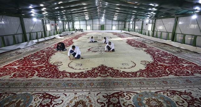 Restoration crew works on the 120-year-old carpet in a warehouse set up in the courtyard of Yıldız Chalet.