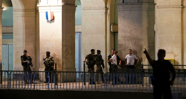 A picture taken on August 19, 2017 shows police officers and soldiers outside the train station of Nimes, following its evacuation after suspicious activities were reported. (AFP PHOTO)