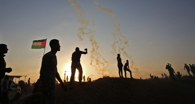 Palestinians protest as tear gas fumes erupt near the border with Israel, east of Khan Yunis, southern Gaza Strip, May 15.