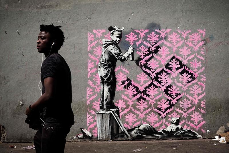 A man walks past a recent artwork by street artist Banksy in Paris on June 24, 2018. (AFP Photo)