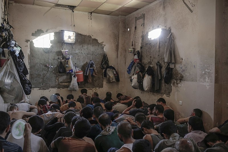 Suspected Daesh members sit inside a small room in a prison south of Mosul, Tuesday, July 18, 2017 (AP Photo)
