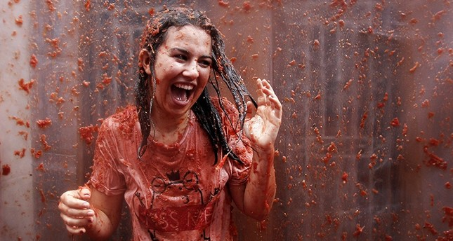 A woman is covered in tomato as she takes part during the traditional annual tomato fight, known as 'Tomatina' in Bunol, eastern Spain, 31 August 2016. (AP Photo)