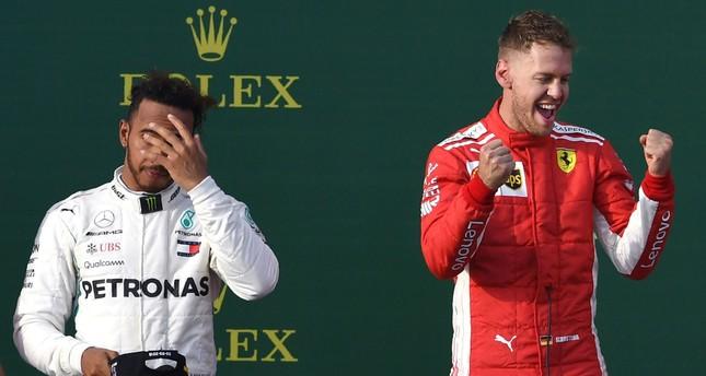 Ferrari's German driver Sebastian Vettel (R) celebrates winning the Formula One Australian Grand Prix beside second-placed Mercedes' British driver Lewis Hamilton (L) in Melbourne.