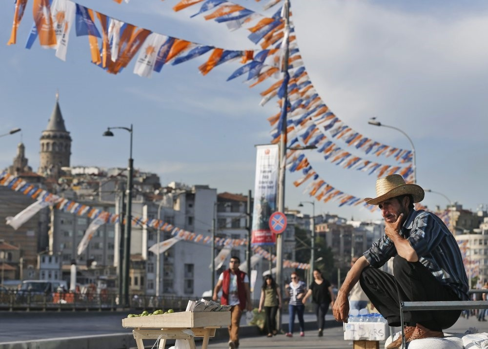A street vendor waits for customers near the iconic Galata Tower surrounded by party flags and banners hung for previous local elections, Istanbul, March 6, 2015.