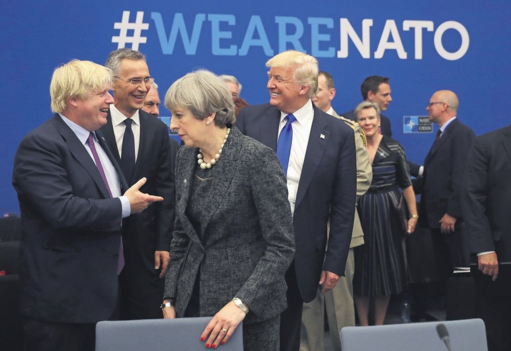 U.S. President Donald Trump jokes with British Foreign Minister Boris Johnson as British Prime Minister Theresa May walks past during a meeting at NATO headquarters during a NATO summit of heads of state and government in Brussels, May 25, 2017.