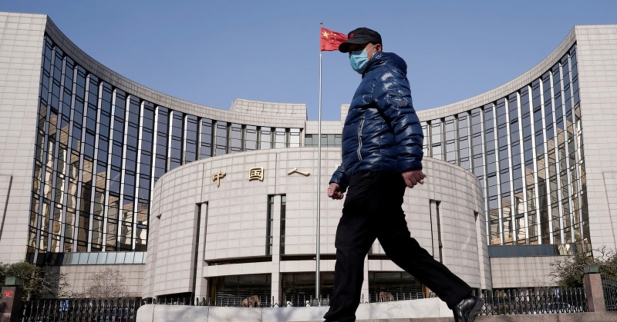A man wearing a mask walks past the headquarters of the People's Bank of China, the central bank, in Beijing, China, as the country is hit by an outbreak of the new coronavirus, February 3, 2020. (Reuters Photo)