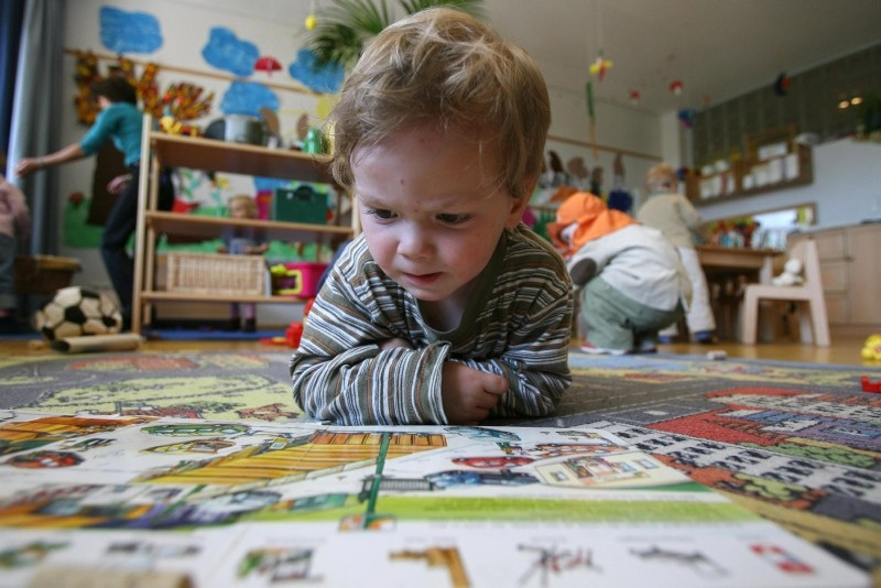 A German toddler of the ,Frogs, group looks at a book at the Spreekita Kindergarten in Berlin 03 May 2007. (AFP Photo)