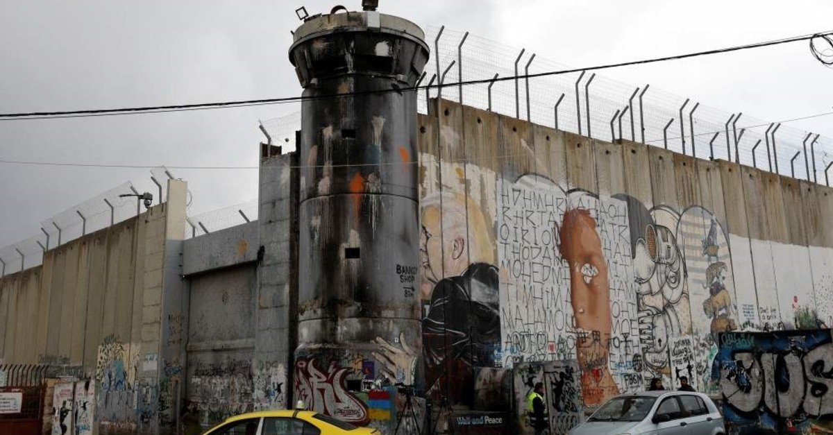 An anti-U.S. President Donald Trump mural is seen on a section of the Israeli barrier and a watchtower in Bethlehem in the Israeli-occupied West Bank, Jan. 29, 2020. (REUTERS Photo)