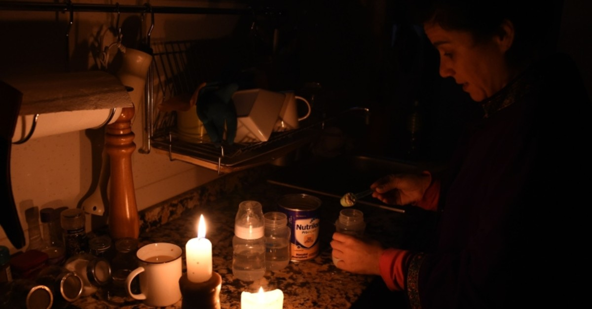 A woman prepares milk bottles using candles at her home in Montevideo on June 16, 2019 during a power cut. (AP Photo)