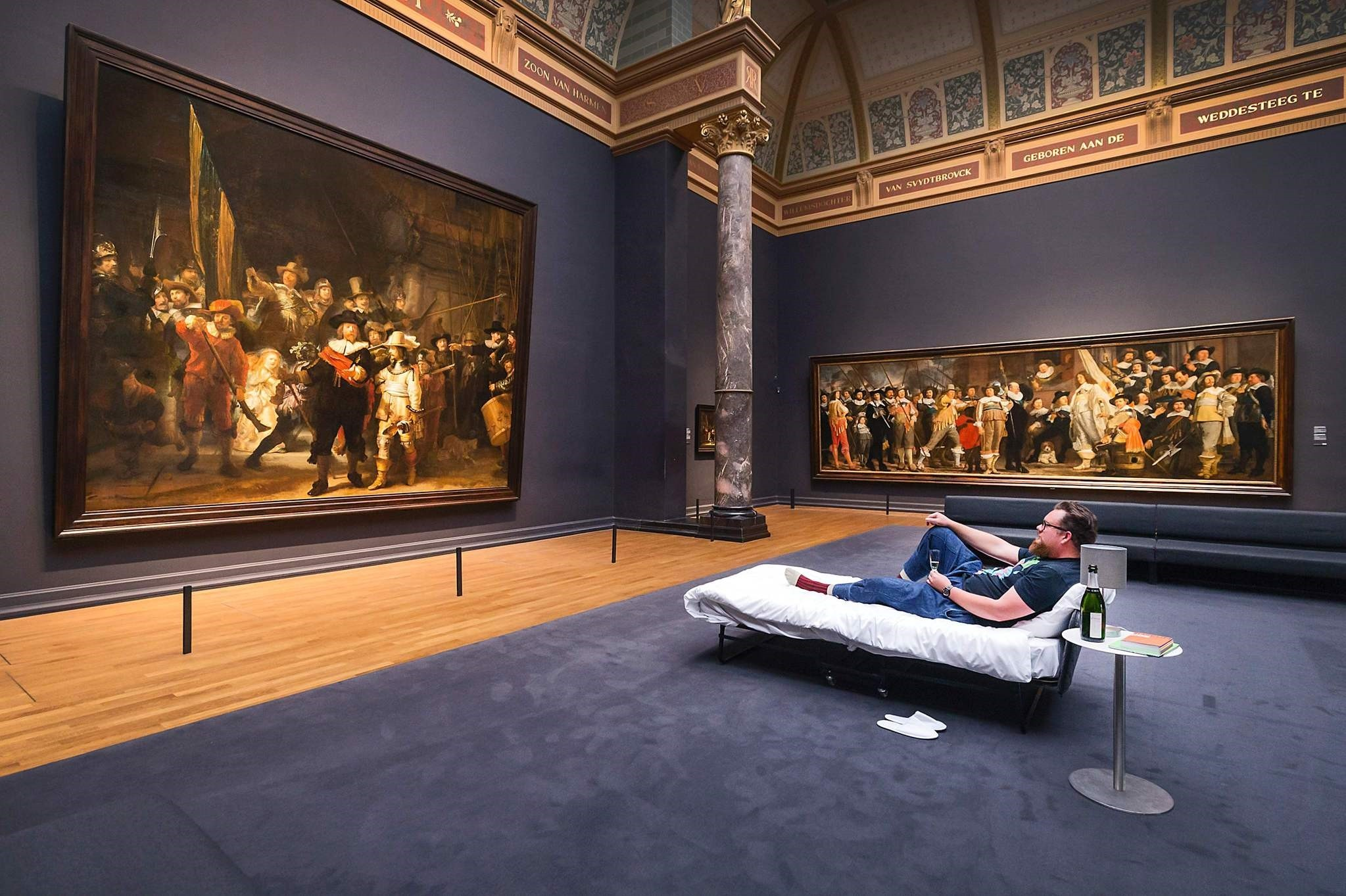 This handout picture released on June 2, 2017 by the Rijksmuseum of Amsterdam shows Stefan Kasper lying in a bed in front of the painting ,The Night Watch, by Dutch painter Rembrandt at the Rijksmuseum of Amsterdam on June 1, 2017. (AFP Photo)