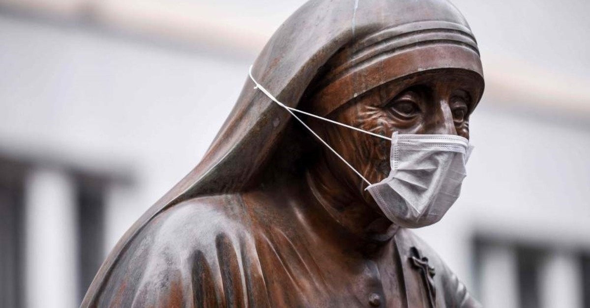 A face mask is placed on the statue of Saint Teresa in Pristina on December 19, 2019. (AFP Photo)