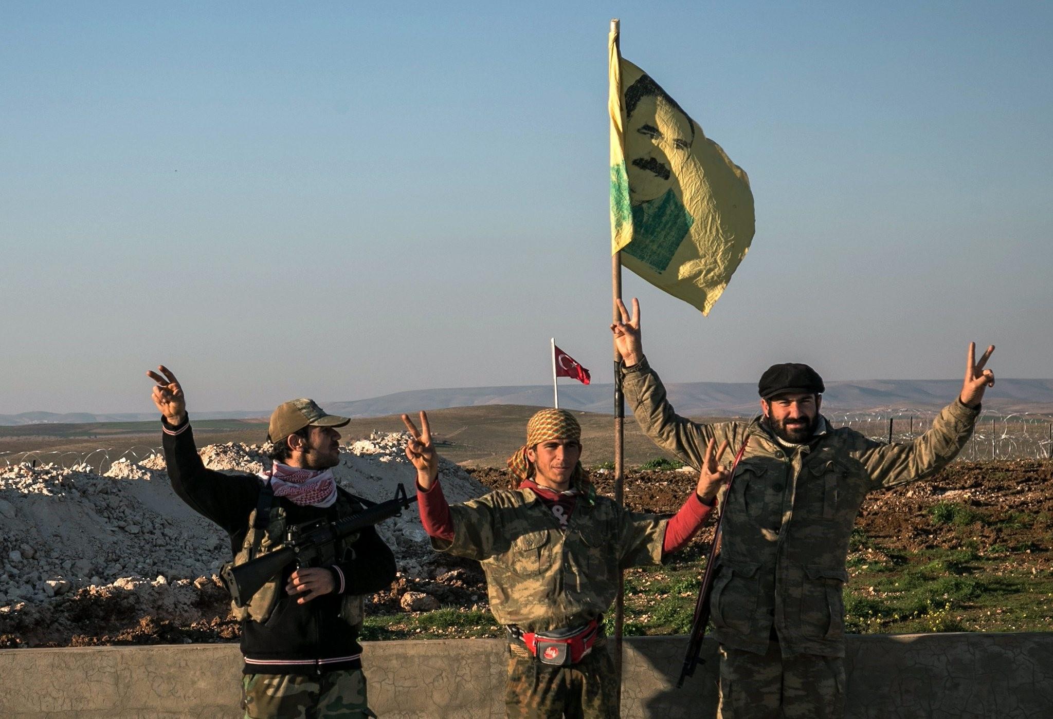 Three YPG militants posing with flag of jailed PKK leader, Abdullah u00d6calan.