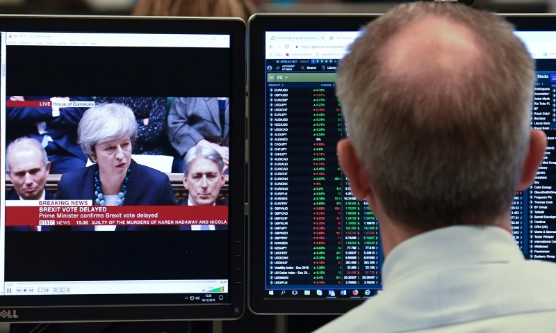 CMC Markets chief market analyst Michael Hewson looks at financial data at the offices of CMC Markets in the City of London on December 10, 2018. (AFP Photo)