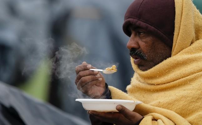 A migrant eats a meal at a makeshift camp in Velika Kladusa, Bosnia-Herzegovina, Nov. 18.
