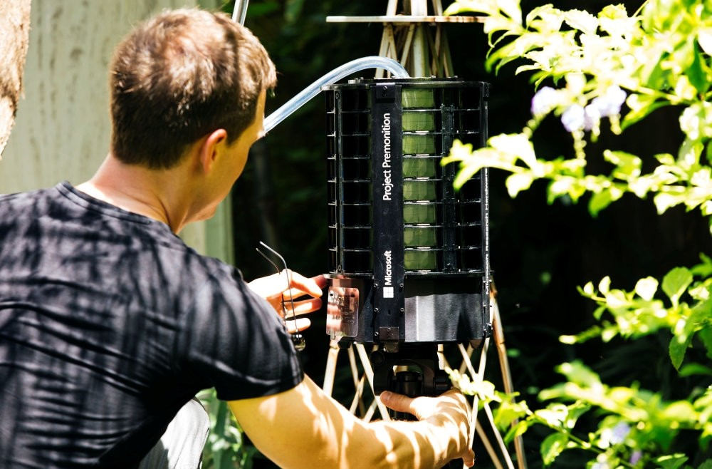 Researcher Ethan Jackson places the Project Premonition mosquito trap in the wild.