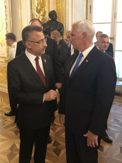 Vice President Oktay speaking with his U.S. counterpart Mike Pence on the sidelines of the ceremony, Warsaw, Poland, Sept. 1, 2019. (AA Photo)
