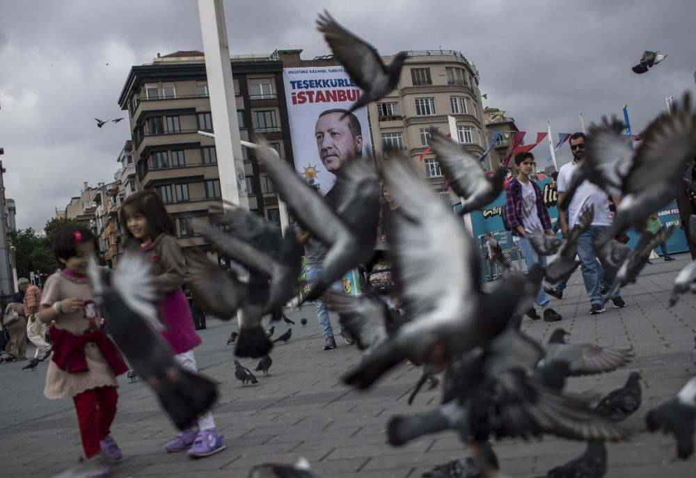 Pedestrians walk in front of a poster of President Recep Tayyip Erdou011fan, which reads ,Thank You, Istanbul,, two days after the June 24 presidential vote in 2018, in Taksim Square, Istanbul.