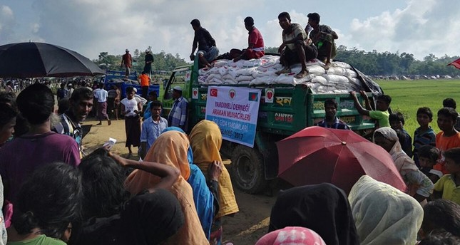 Rohingya refugees wait next to a truck carrying food aid provided by the Turkish Yardımeli aid agency, at the Tamfali refugee camp, in Bangladesh, Sept. 22, 2017. (AA Agency)