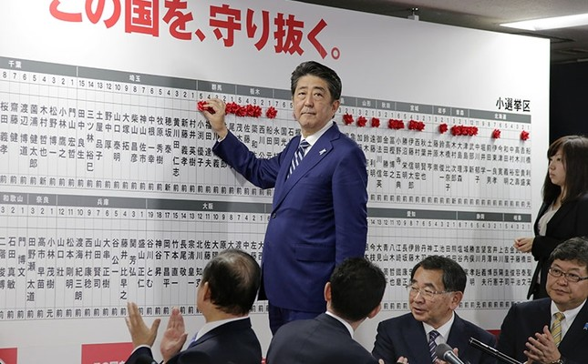 Japanese PM Shinzo Abe (C-Standing) puts a red rose on name of a party's candidate to be elected in the Lower House election as party's senior members applaud at headquarters of the ruling LDP in Tokyo, Japan, Oct. 22, 2017. (EPA Photo)