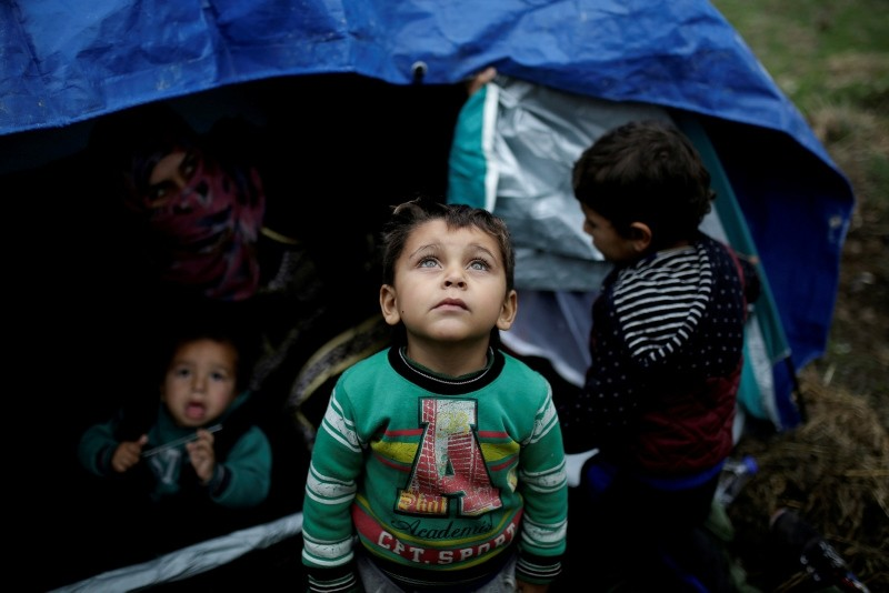 A Syrian refugee boy stands in front of his family tent at a makeshift camp for refugees and migrants next to the Moria camp on the island of Lesbos, Greece, November 30, 2017. (Reuters Photo)