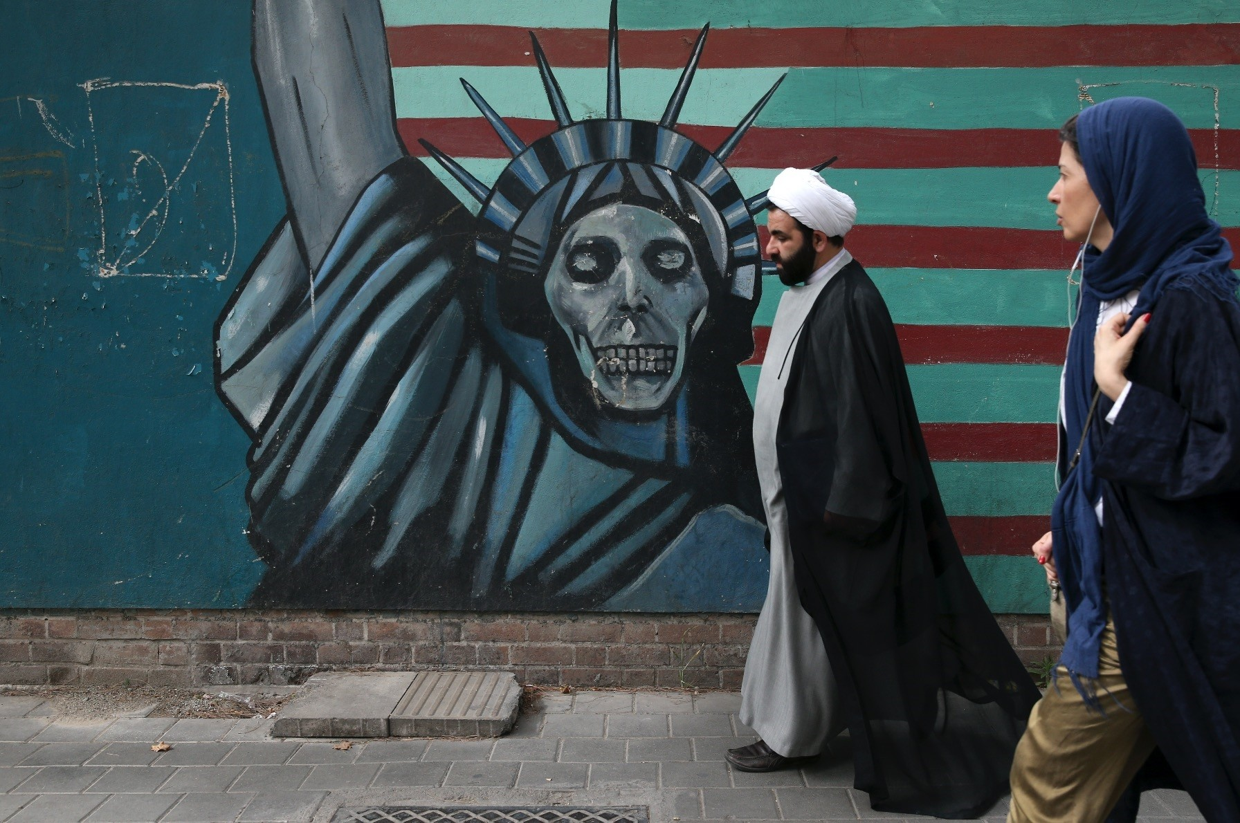 A cleric and a woman walk past an anti-U.S. mural painted on the wall of the former U.S. Embassy in Tehran, Iran, May, 8.