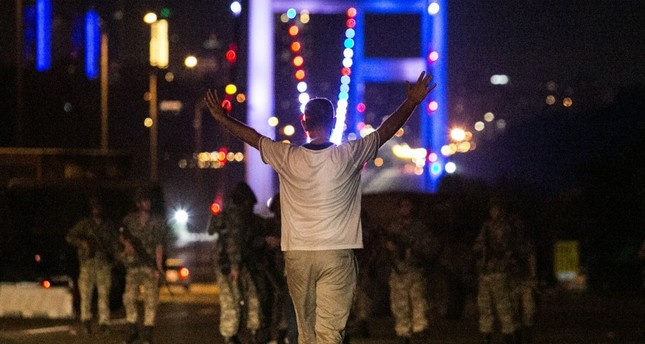 A civilian approaches Gülenist putschist officers with his hands up at the entrance to the July 15 Martyrs Bridge, in Istanbul on the night of July 15, 2016 when Gülenist terrorists attempted a deadly coup, killing 249 people and wounding thousands.