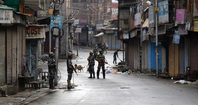 Indian paramilitary soldiers stand guard on a deserted street during the curfew in Srinagar, Kashmir, Aug. 8, 2019.