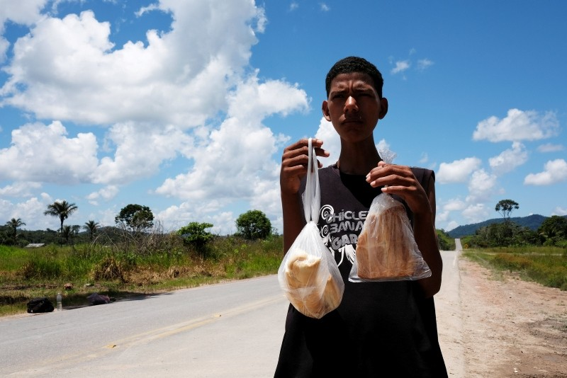 A man from Venezuela's Aragua state poses with bread loaves as he attempts to hitchhike toward Boa Vista city at the Pacaraima border control, Roraima state, Brazil August 10, 2018. (Reuters Photo)