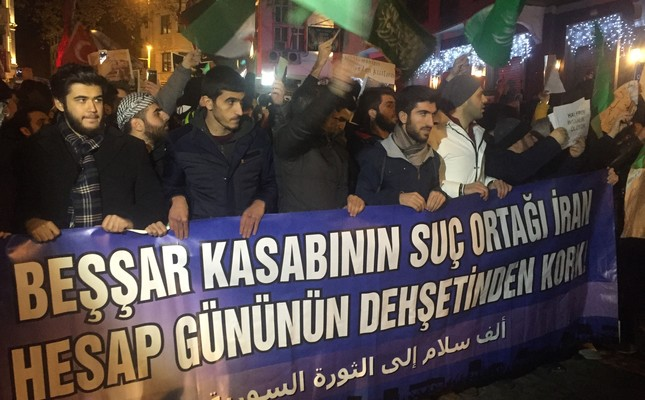 """People gathered outside Istanbul consulate of Iran hold a banner reading """"Iran, accomplice of Bashar the Butcher, fear the horror of day of reckoning."""""""