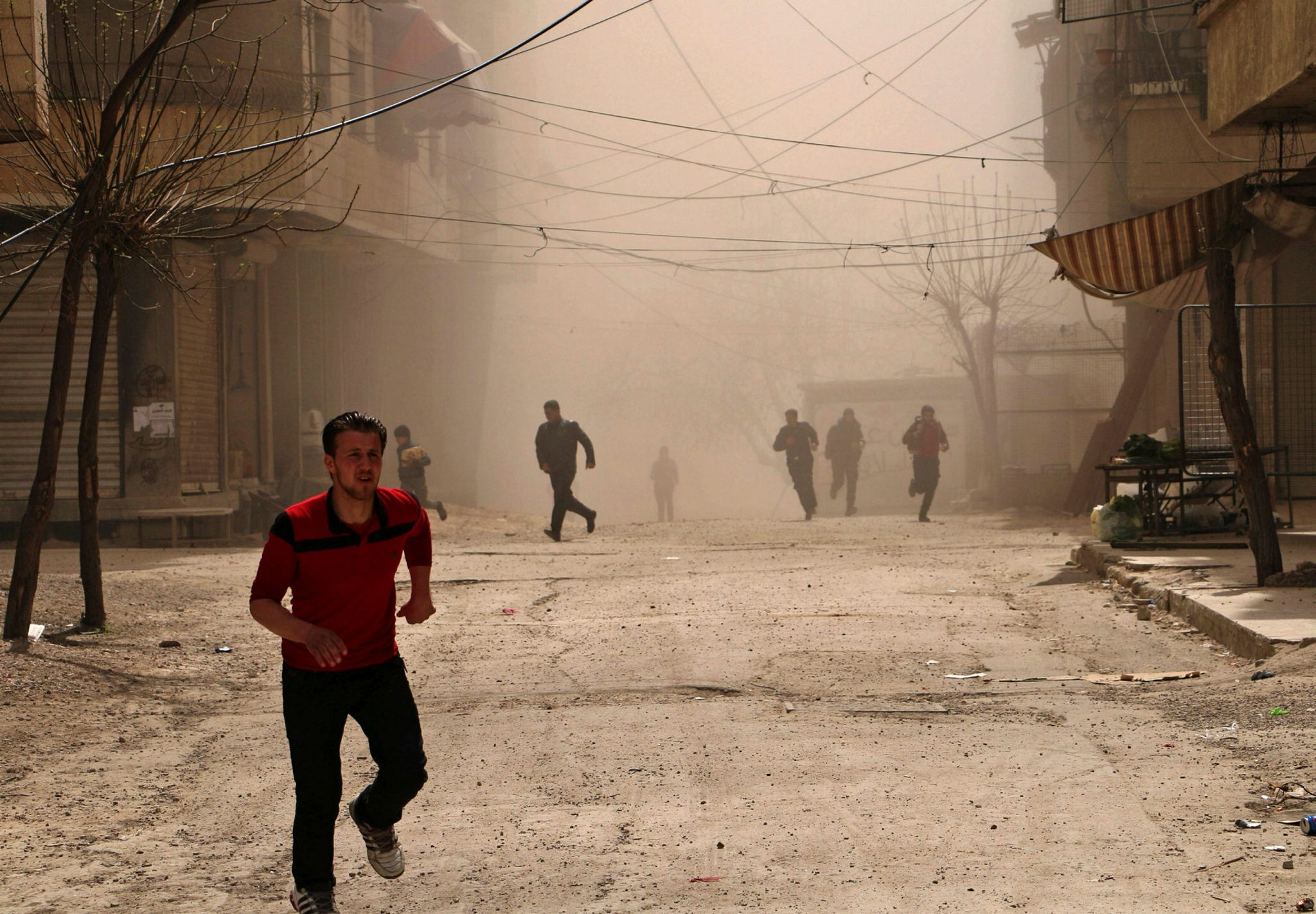 Syrians run for cover as smoke billows following an airstrike on Ain Tarma, in the eastern Ghouta area (AFP Photo)