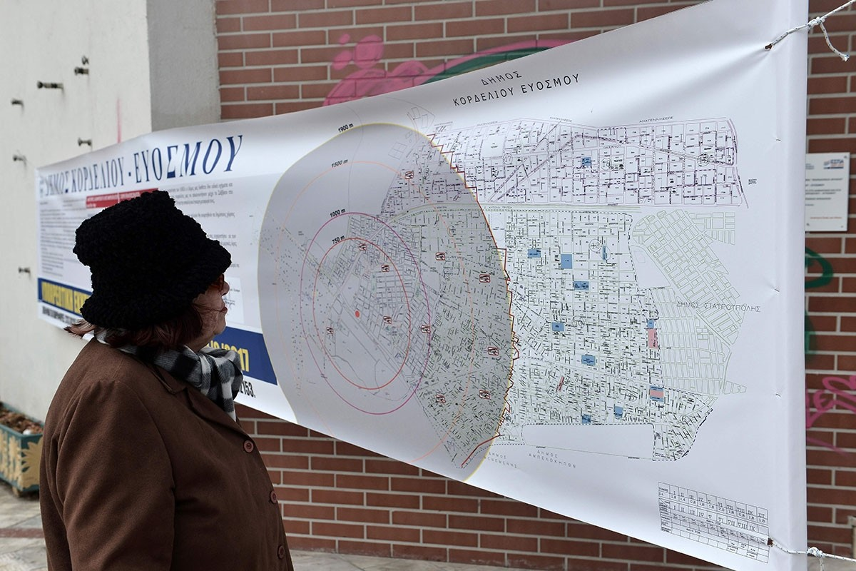 A resident looks at a map showing the radius of the evacuation area, ahead of an operation to defuse a World War II bomb in Kordelio, a suburb of Thessaloniki, on February 12, 2017. (AP Photo)