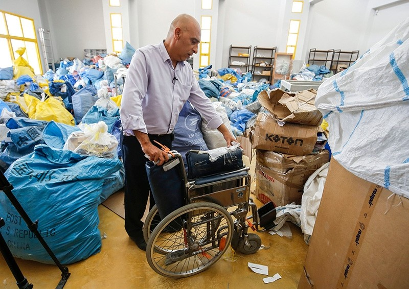 Ramadan Ghazawi, a Palestinian official at the post office in occupied West Bank city of Jericho, stands next to a folded wheelchair, one of many items of previously undelivered mail which has been withheld by Israel, on Aug. 14, 2018. (AFP Photo)