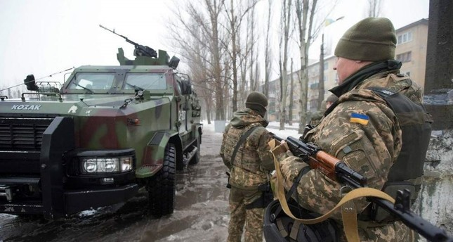 Ukrainian servicemen stand near their armed personal carrier in the eastern city of Avdiivka, Donetsk.