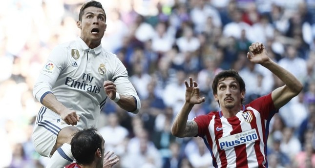 Real Madrid's Portuguese striker Cristiano Ronaldo L tries to score next to Uruguayan defender Diego Godin C of Atletico Madrid during the Primera Division match at Santiago Bernabeu stadium in Madrid on Apr. 8.