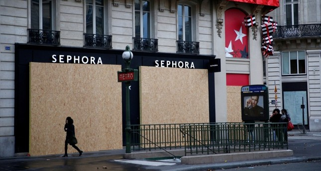 A woman walks past a closed shop protected by wood panels near the Opera district during a national day of protest by the yellow vests movement in Paris, France, December 8, 2018. (Reuters Photo)