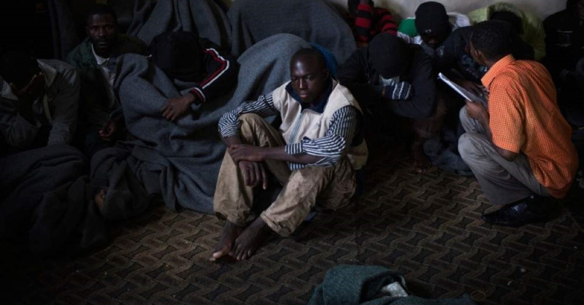 Migrants cover themselves with blankets in a detention center in the Abu Salim district on the outskirts of Tripoli, Libya. (AP Photo)