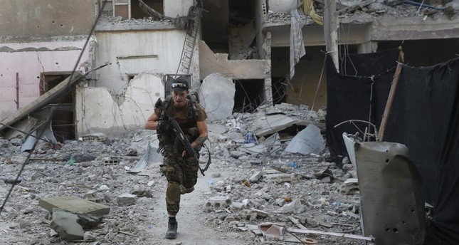 A U.S.-backed YPG terrorist runs in front of a damaged building as he crosses a street on the front line in Raqqa, Syria, July 27.