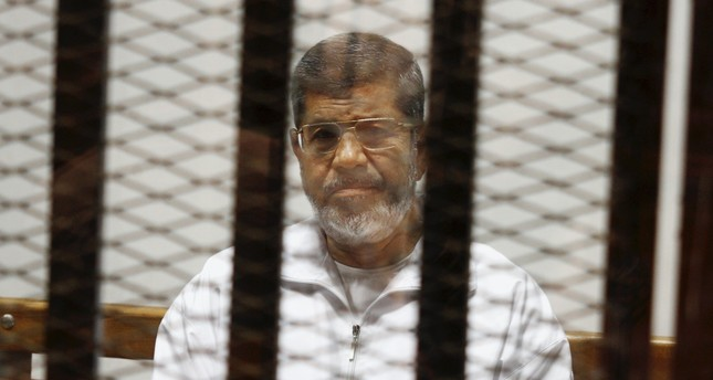 Egypt's first democratically-elected President Mohammed Morsi sits in a defendant cage in the Police Academy courthouse, Cairo, May 8, 2014.